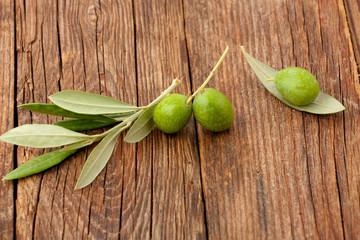 Fototapete - Olive rami di ulivo e foglie su un piano in legno