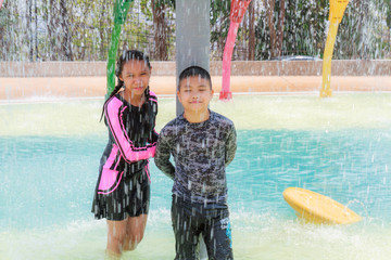 Asian boy and girl play water park in summer.