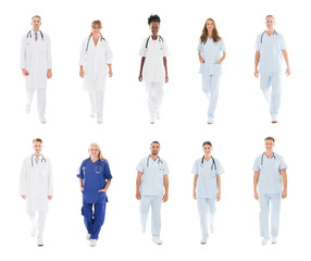 Doctors With Medical Workers Walking Against White Background