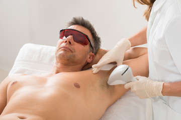 Beautician Giving Hair Removal Treatment To Man