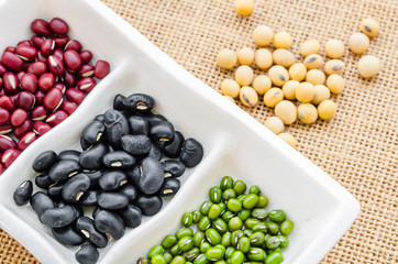 Multicolored beans in white bowl .