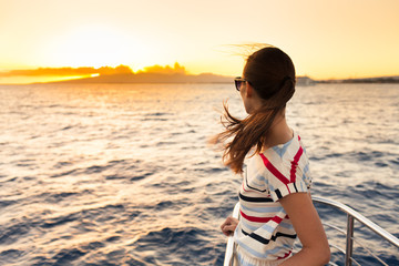 Young woman watching the sunset on a yacht.
