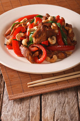 chicken pieces fried with vegetables and cashew nuts closeup on a plate. vertical