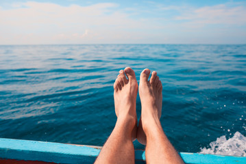 Feet relaxing on a boat. Travel and adventure  concepts.