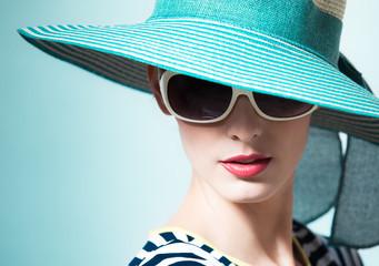 High fashion model wearing blue hat.