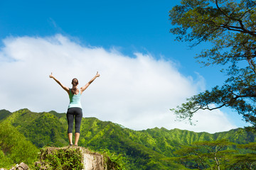 Fit female feeling free in a green nature setting.