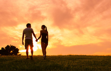 Couple holding hands and walking into the beautiful sunset.
