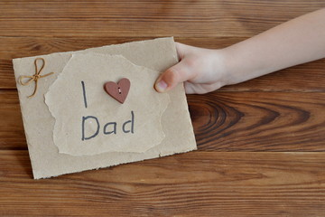 Child holds a card with a message I love dad. Postcard with a button heart, a bow of brown cord. Easy homemade gift idea for dad. DIY Father's day card. Gift idea for dad from daughter. Craft concept