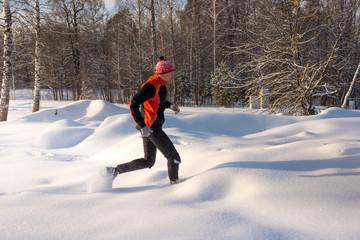 Trail runner in winter forest. Running across the snowy fields