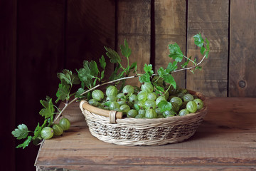 Green gooseberries in a basket on the table.