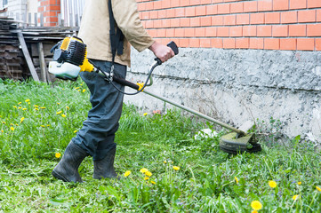 Man in work clothes mows the grass and dandelions lawn mower in