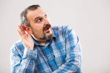 Portrait of man who is trying to hear something