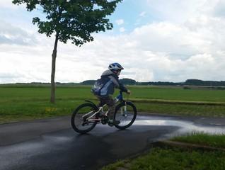 Kind fährt mit Fahrrad durch Pfützen