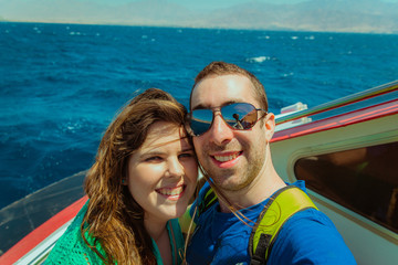 Happy couple sailing on a boat and taking selfie with smartphone