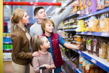 Parents with two kids choosing crispy flakes in shop