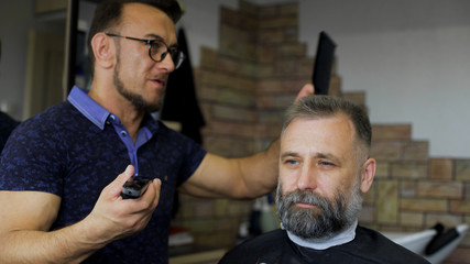 Cozy Barbershop, is engaged in a professional stylist haircut men aged. A respectable businessman in the client's chair.