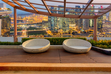 Relax corner on condominium rooftop garden with chairs on Landscape of the Singapore financial district and business building background, Landmark concept