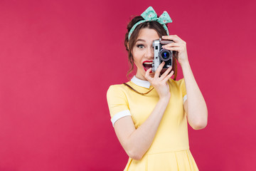 Happy beautiful pinup girl taking photos using vintage camera