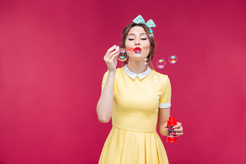 Attractive pinup girl in yellow dress blowing soap bubbles