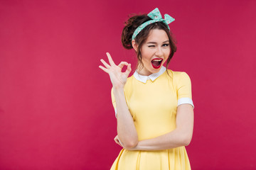 Happy attractive pinup girl in yellow dress showing ok sign