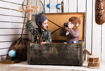 sisters playing with wooden plane in chest