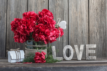 Dark red peonies in a decorated glass jar and home decoration