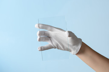 New features of glass or plastic research, hand in glove holding rectangular piece of transparent material