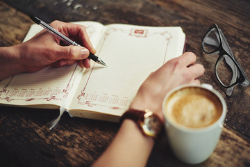 Woman hands with pen writing memo in her diary. Young female journalist creating new article sitting at the table in coffee shop.
