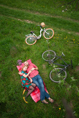 Young romantic couple lying on a red blanket at the fresh green grass near the two lying bicycles. View from above