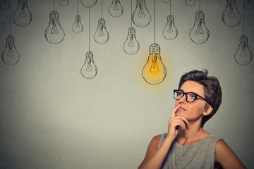 Portrait thinking woman in glasses looking up with light idea bulb above head