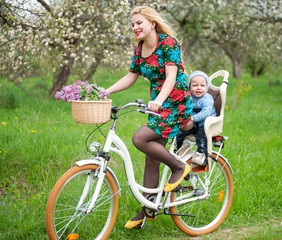 Blonde female with long hair in dress riding city bicycle with baby in bicycle chair, in the basket lay a bouquet of lilacs, against the background of blooming fresh greenery in spring garden
