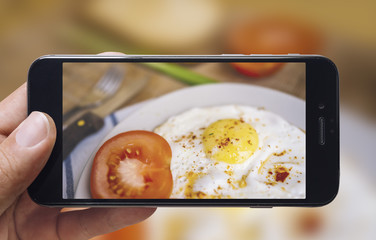 Taking picture of fried eggs and tomato with mobile phone. Phone in male hands.On the plate there is 2 fried eggs, tomato, fork and knife. Vintage style.