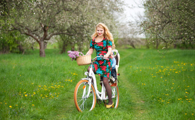 Happy mother with long blonde hair in dress riding city bicycle with baby in bicycle chair, in the basket lay a bouquet of lilacs, against the background of blooming fresh greenery in spring garden