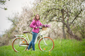 Smiling brunette woman wearing purple jacket and jeans with a vintage white bicycle and lilac flowers basket, against the background of blooming trees, dandelions and fresh greenery in spring garden