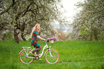 Happy woman with long blond hair wearing flowered dress and yellow shoes riding a vintage white bicycle. Blooming trees, dandelions and fresh greenery in spring garden on the background