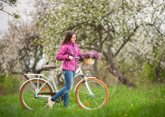 Beautiful woman wearing purple jacket and jeans with a vintage white bicycle and lilac flowers basket  in spring garden