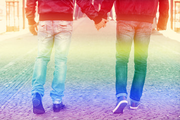 two men holding hands with the rainbow colors for gay pride