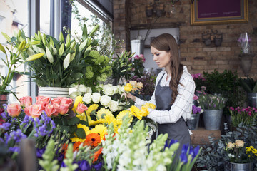 Female Florist At Work In Shop