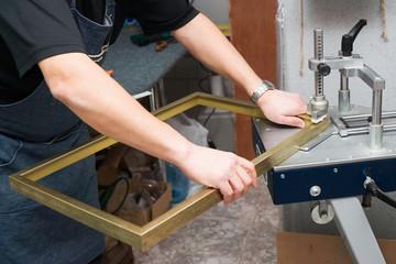 Craftsman working on frame in frameshop. Professional framer. Top view.