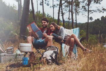 Young couple camping and looking at map