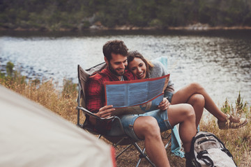 Camping couple looking at a travel map