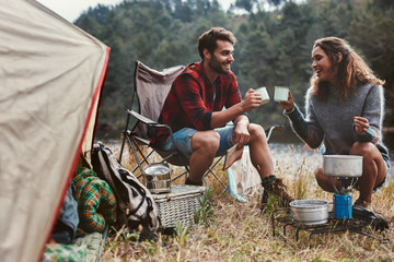 Happy young couple drinking coffee by tent at campsite