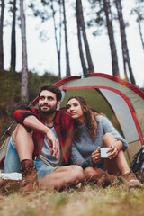 Young couple sitting in front of tent in forest