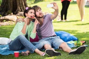 Man and woman taking photo at picnic