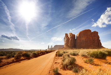 sun shining on a dirt road in monument valley