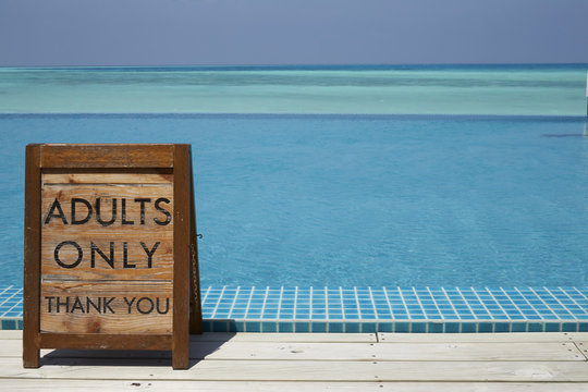 Adults only sign by an infinity pool with ocean beyond