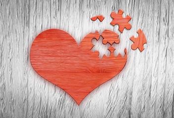 Red wooden puzzle heart on grey wooden background
