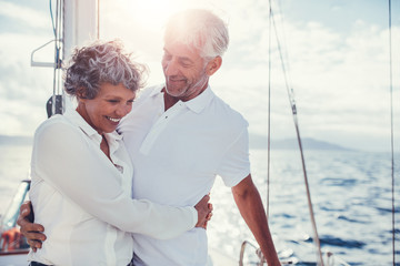Romantic senior couple standing on sailboat