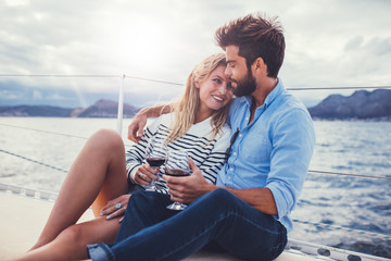 Romantic couple sailing on a boat with wine