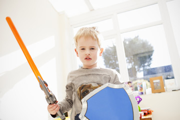 Boy Playing With Plastic Sword And Shield At Home